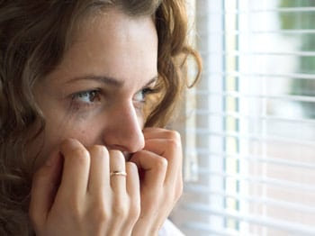 women staring out window having panic attack